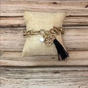 Gold bracelet with black tassel